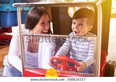 excited woman with little boy driving a car on merry-go-round - stock photo