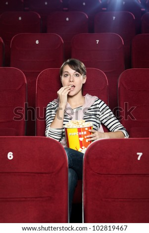 Excited woman with popcorn in the movie theater - stock photo