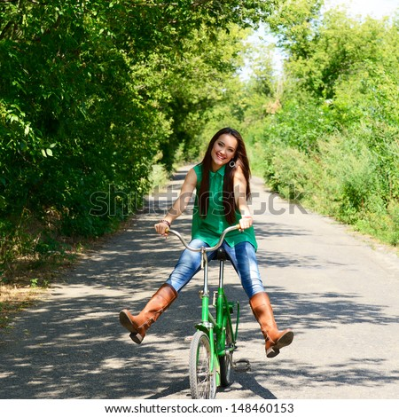 excited young beautiful woman happy riding in retro bicycle, summer outdoor - stock photo