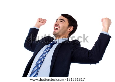 Excited young businessman clenching fists - stock photo