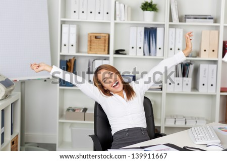 Excited young businesswoman with arms raised sitting on chair at office desk - stock photo