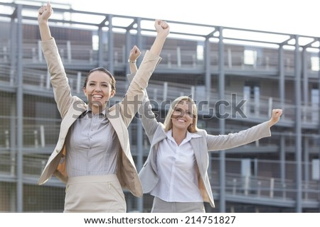 Excited young businesswomen with arms raised against office building - stock photo