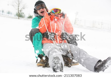 Excited young couple sledding in snow - stock photo