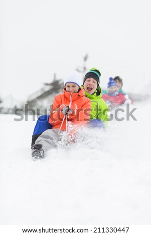 Excited young friends sledding in snow - stock photo