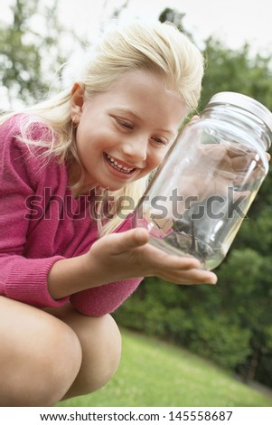 Excited young girl looking at grasshopper in jar outdoors - stock photo