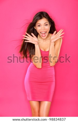 Excited young lady portrait. Woman celebrating success on pink background. Beautiful smiling happy mixed race Caucasian / Chinese Asian brunette fashion model. - stock photo