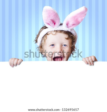 Excited young male child wearing rabbit ears holding empty copy space board during a surprise easter sale - stock photo