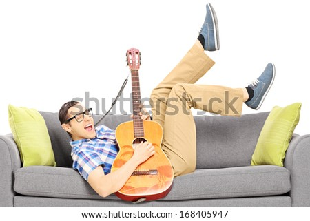 Excited young male lying on a modern couch and playing a guitar isolated on white background - stock photo