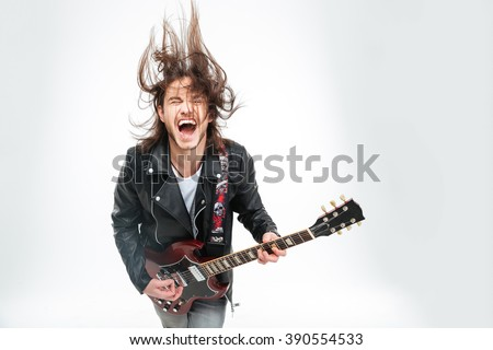 Excited young man in black leather jacket with electric guitar shouting and shaking head over white background - stock photo