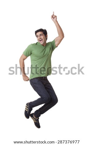 Excited young man jumping over white background - stock photo