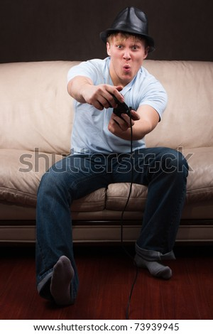 excited young man playing video games on gray background - stock photo