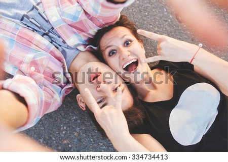 Excited young people lying down. Teenager pair doing a selfie while lying on road. Top view. - stock photo