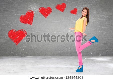 excited young woman being in love, standing on one leg - stock photo