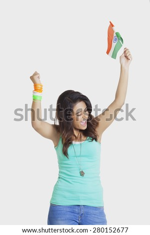 Excited young woman cheering with clenched fists while holding Indian flag over white background - stock photo