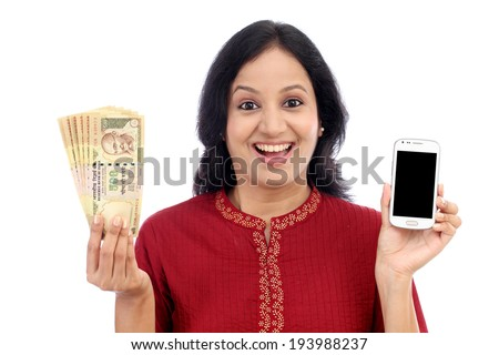Excited young woman holding Indian currency and mobile phone - Mobile banking - stock photo