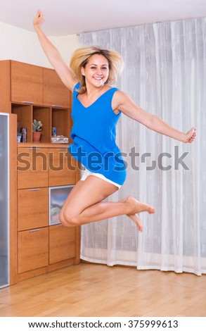Excited young woman jumping full of happiness in interior - stock photo