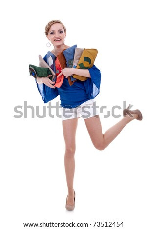 excited young woman standing on one leg and holding a bunch of purses - stock photo