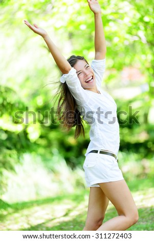 Excited young woman with arms raised standing in park. Happy mixed race Asian / Caucasian female is enjoying on sunny day. She is in casuals. - stock photo