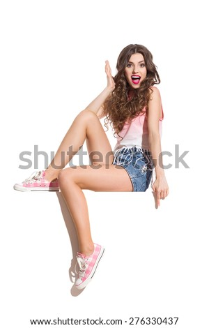 Excitement on a Banner. Shocked sexy woman in pink top, jeans shorts and pink sneakers sitting on the white banner and pointing down. Full length studio shot isolated on white. - stock photo