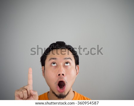 Exciting face of Asian man looking up. - stock photo