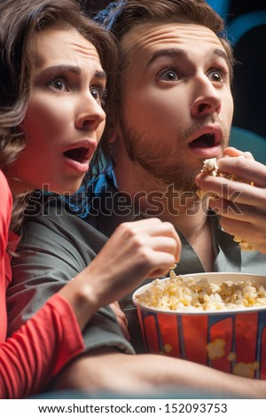 Exciting movie. Close-up of shocked young couple eating popcorn and drinking soda while watching movie at the cinema - stock photo