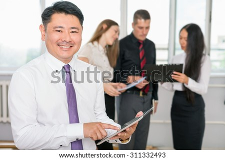 Executive asian boss using tablet pc with his successful business team at background. Multiracial people is a good addition for running a successful business - stock photo
