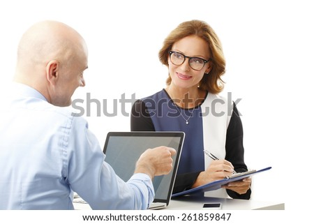 Executive businessman giving advise to business woman while working with laptop. Isolated on white background.  - stock photo