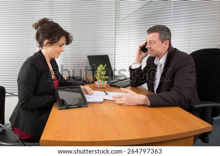 Executive businessman working on laptop computer at desk, in office, calling on mobile phone - stock photo