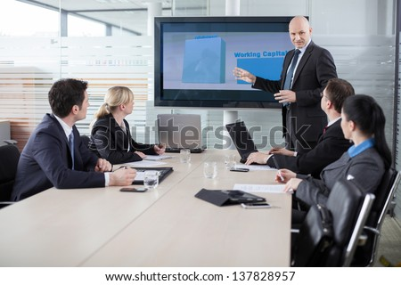 Executive explaining business plans to his employees - stock photo