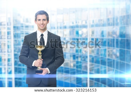 Executive keeping gold cup, blue background. Concept of victory and success - stock photo