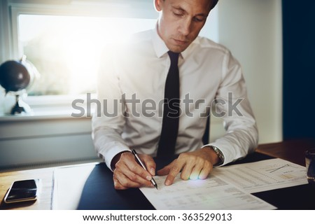 Executive male working at desk looking at documents and accounts holding a pen and looking concentrated and serious - stock photo