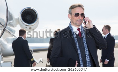 executive manager in front of corporate jet using a smart phone - stock photo