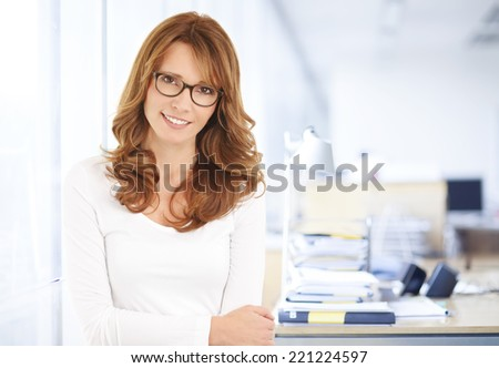 Executive middle age businesswoman standing at office. Business people. - stock photo