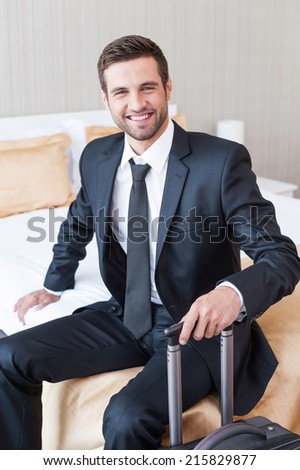 Executive on the Go. Confident young businessman in formalwear carrying suitcase and smiling while sitting on the bed in hotel room  - stock photo