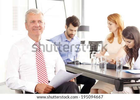 Executive senior businessman smiling at meeting. Background with colleagues. - stock photo