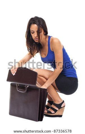 executive woman squatting and looking inside a briefcase - stock photo