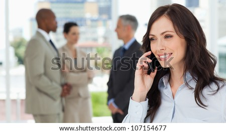 Executive woman talking on the phone in a relaxed way with her team behind her - stock photo