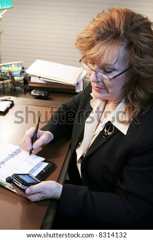Executive Woman transferring notes from PDA - stock photo