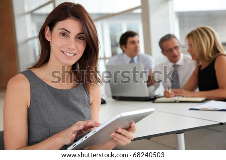 Executive woman working on electronic tab - stock photo