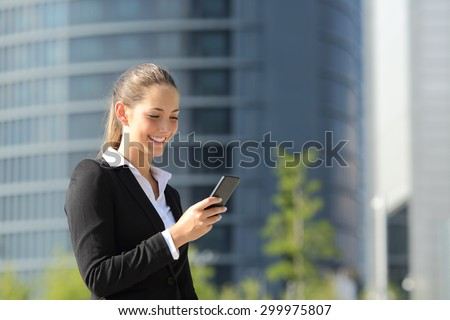 Executive working with a mobile phone in the street with office buildings in the background - stock photo