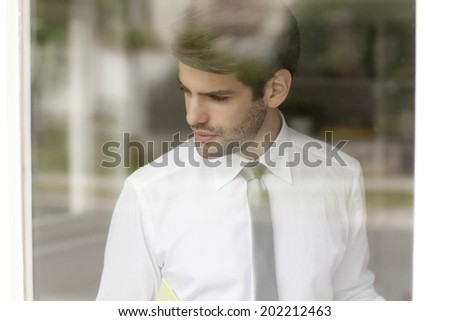 Executive young businessman standing behind window. Small Business. - stock photo
