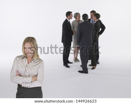 Executives in group with businesswoman left out - stock photo