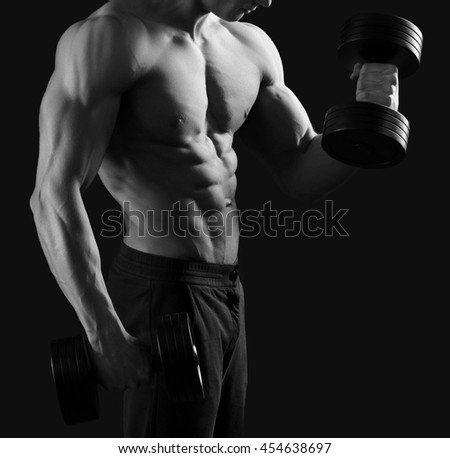 Exercise equipment. Black and white cropped shot of a muscular fit and toned fitness man lifting dumbbells - stock photo
