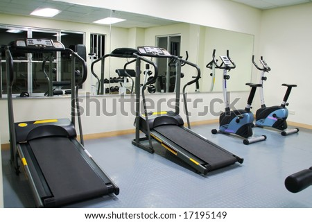 exercise gym with large mirrors, treadmills and stationary bikes - stock photo