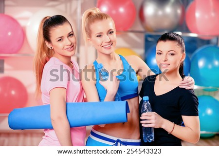 Exercise makes us happy. Three beautiful young women in sports clothing smiling and holding sports tools while standing in the gym with bottles of water - stock photo