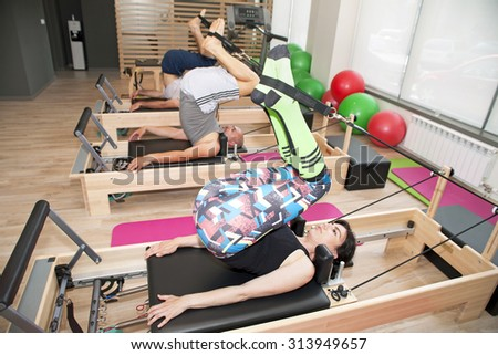 Exercise on pilates device reformer at gym - stock photo