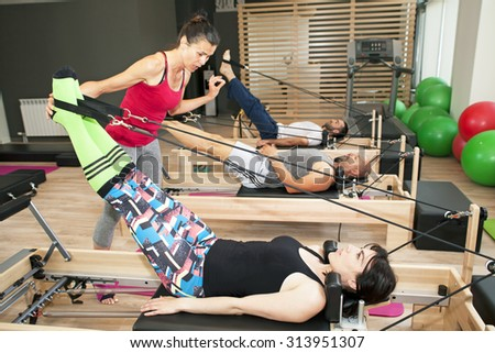 Exercise on pilates device reformer with instructor at gym  - stock photo