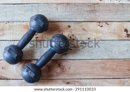exercise weights - old dumbbell on  a wooden background. - stock photo