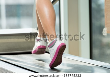 Exercising On A Treadmill - Close-Up Of Female Legs Running On Treadmill - Blurred Motion - stock photo