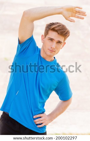 Exercising outdoors. Handsome young man doing stretching exercises while standing outdoors  - stock photo